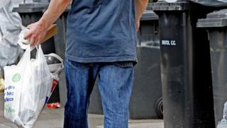 Man taking rubbish into bins