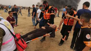 Palestinian medics carry an injured Palestinian woman during a protest near the Gaza-Israel border fence on 4 May 2018