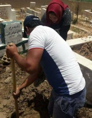 Man helping to dig up grave