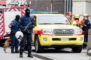 Several police officers hold guns in Molenbeek