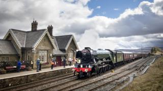 The Flying Scotsman passes Ribblehead Train Station in the Yorkshire Dales National Park