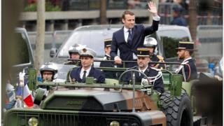 Президент Макрон приветствует толпу на Елисейских полях