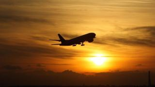 Plane takes off from Heathrow Airport at sunset