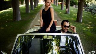 Casal em carro de luxo