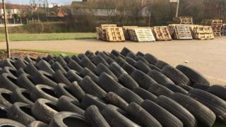 Tyres and pallets have been stockpiled along a public path on the greenway