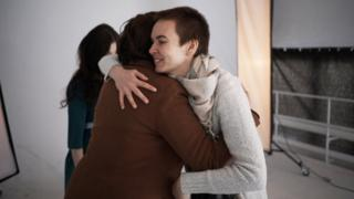 Photographer Dasha Buben greets one of the women arriving to the photo shoot