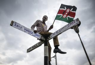 "A supporter of The National Super Alliance (NASA) opposition coalition and its presidential candidate Raila Odinga sits on top of a street sign post that has been relabeled ""Judge Maraga Street"", referring to Chief Justice David Maraga, and ""Orengo Street"", referring to NASA""s lawyer James Orengo, in front of the Supreme Court in central Nairobi, Kenya, 01 September 2017. Kenya""s Supreme Court on 01 September overturned the re-election of President Uhuru Kenyatta and ordered a re-run of the election within 60 days, citing irregularities. Ecstatic opposition supporters marched through the city to celebrate ""historic"" court decision."
