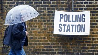 Man walks to polling station in pouring rain