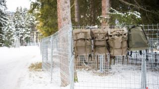 Army backpacks hang on the security fences installed by Swiss army members ahead of the upcoming World Economic Forum at Davos, Switzerland (7 January 2016)