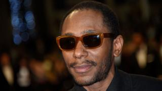 """This file photo taken on May 17, 2015 shows US rapper Yasiin Bey formerly Mos Def posing as he arrives for the screening of the film """"Amy"""" at the 68th Cannes Film Festival in Cannes, southeastern France"""