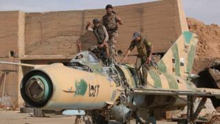Tabka'daki askeri üssü IŞİD'in elinden alan SDG üyeleri, 9 Nisan'da burada ele geçirdikleri kullanılamaz haldeki savaş uçağıyla poz verdi