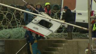 A panel from the helicopter is brought ashore