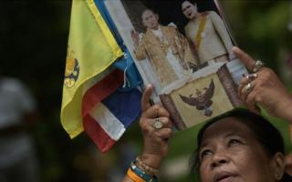 A Thai well-wisher holds up a picture of Thai King Bhumibol Adulyadej and Queen Sirikit as she offers prayers for his recovery at the Siriraj hospital in Bangkok on 6 October 2014.