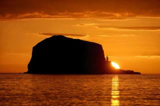 The sun rises over Bass Rock lighthouse in the Firth of Forth near North Berwick, East Lothian