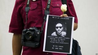 A photojournalist holds a white flower and a picture of murdered photojournalist Ruben Espinosa during a demonstration on 2 August, 2015