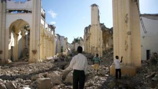 Haitians walk through the remains of the Notre Dame Cathedral in Port-au-Prince on the first anniversary of the 2010 quake