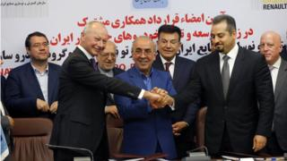 Thierry Bollore (L), deputy director in Competitiveness at Renault Group along with Mansour Moazami (C) Chairman of the Board of Directors of IDRO Group, along with Kourosh Morshed Solouki (R), deputy director of the Iranian Automobile Importers Association shake hands as Commerce Minister Mohammad Reza Nematzadeh (2-L back), looks on after during signing documents in Tehran, Iran, 07 August 2017.
