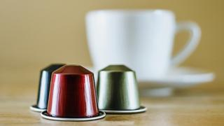 Coffee capsules in front of a coffee cup