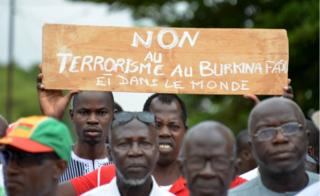 """Protestors march holding a placard they take part in a rally """"no to barbarism"""" in central Ouagadougou on August 19, 2017, after a recent attack in the capital of Burkina Faso in which 18 people were killed. Gunmen killed nine locals and nine foreigners as they dined on the terrace of a Turkish restaurant in Ouagadougou late August 13."""