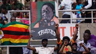 Supporters hold a portrait of Zimbabwe's new President Emmerson Mnangagwa during his inauguration on 24 November 2017 in Harare