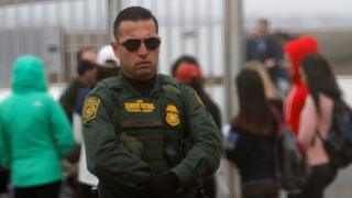 A US Border Patrol agent looks on at people along the US-Mexican border.