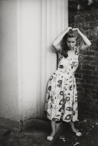 Alison Owen fixes her hair in a doorway, circa 1984