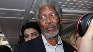 Morgan Freeman mira hacia un lado, como con sorpresa mientras los periodistas lo abordan.