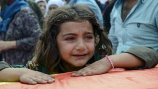 A girl cries as she leans on the coffin of a relative killed during clashes between Turkish forces and the PKK in the city of Cizre