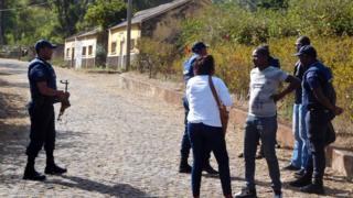 Local authorities stand near the entrance to the Monte Txota military barracks, on the island of Santiago, Cidade da Praia, Cape Verde, 26 April 2016