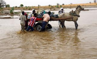 Displaced people carry their belongings to get away from flood during heavy rain at Nyala locality in South Darfur, Sudan 3 June 2017.