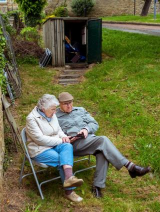 An elderly couple sat in a park. Wetherby, West Yorkshire.