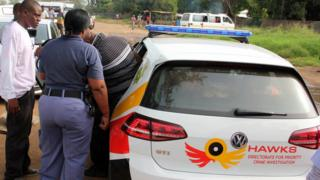 Members of the Hawks unit make an arrest with a branded police car