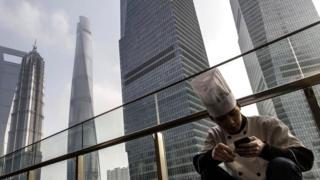 Китаец со смартфоном на фоне небоскребов