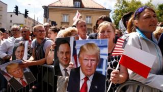 Abanyagihugu bumviriza ijambo rya Trump bari bitwaje ivyapa vy'ifoto yiwe (hagati i buryo) n'iya Prezida wa Pologne Andrzej Duda