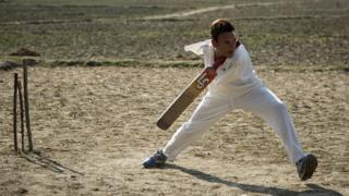 Amir holds the cricket bat between his neck and shoulder