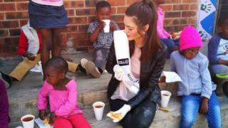 Miss South Africa wearing gloves with food around Soweto orphans
