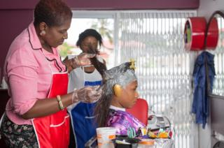 St Claire Adotey dey do a woman's hair for her salon