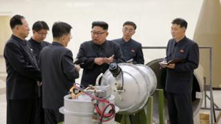 Kim Jong-un, centre, gestures at men in dark military suits over what appears to be a complicated bomb or warhead