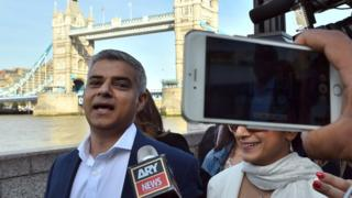 Sadiq Khan is photographed with a mobile phone in front of Tower Bridge, London
