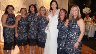 Six wedding guests in identical dresses pose for a photograph with the bride