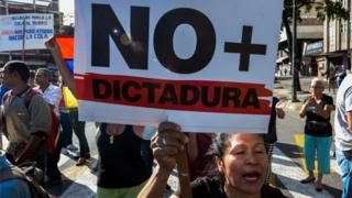 """A Venezuelan opposition activist, holds a sign reading """"No more dictatorship"""" and chants slogans against the government of President Nicolas Maduro, during a march along a street of Caracas on March 31, 2017."""