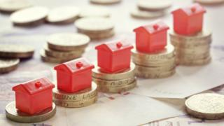Miniature red houses resting on pound coin stacks