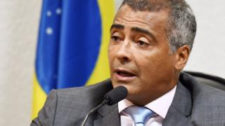 Romario pictured at microphone in front of flag at 2015 event