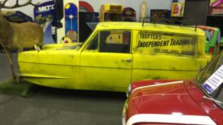 A replica Del Boy Reliant Robin car with three wheels. The yellow car has the trademark 'Trotters Independent Trading Co' logo on the side.
