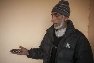 Mohammad Yaqoob holds empty bullet shells in his palm.