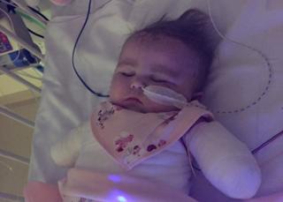 Kia Gott sleeping in a hospital crib