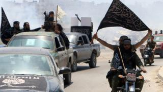 Fighters from Al-Nusra Front drive in Aleppo flying Islamist flags as they head to a front line, on May 26, 2015