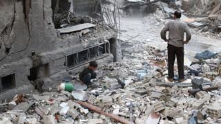 Şam'ın yakınlardaki Duma'da yerle bir olmuş bir bina önünde bir adam ve bir çocuk
