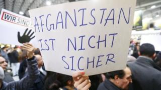 د افغان کډوالو پر بېرته ستنولو اعتراض کوونکو پلاکارډ په لاس کې نیولی چې پرې لیکل شوي افغانستان امن نه دی