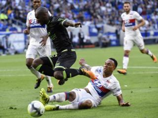 """Guingamp""""s French-Congolese defender Jordan Ikoko (L) vies with Lyon""""s Dutch defender Kenny Tete (bottom) during the French L1 football match Lyon (OL) vs Guingamp (EAG), on September 10, 2017 at the Groupama stadium in Décines-Charpieu near Lyon, southeastern France."""